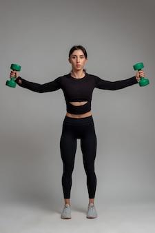 スタジオでダンベルで肩のトレーニングを行うスポーティな女の子