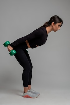 Sporty girl performing triceps kickback with dumbbells on grey surface