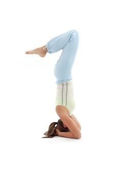Salambasirsasanaを練習するスポーティな女の子が倒立をサポート