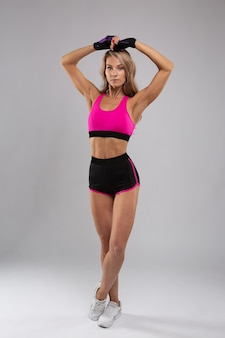 Sporty girl raised her hands up showing off her beautiful biceps and abs