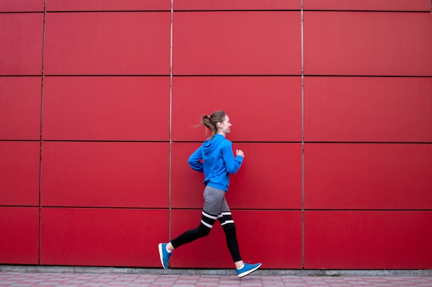Sporty girl runs against a red wall in the street
