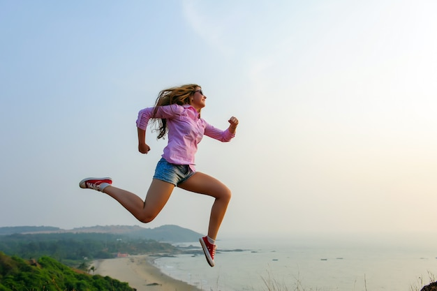 Sporty girl in shirt, shorts and sneakers depicts running in the air on a hill against the sea