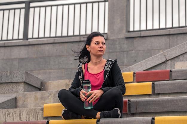 階段に座っているスポーティな女の子