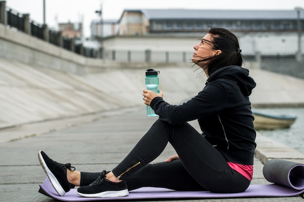 Sporty girl sitting with bottle of water