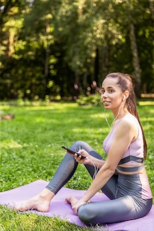 Sporty girl sitting on a yoga mat listens to a music in the park
