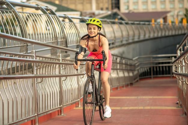 スポーティーな女の子。自転車で明るいスポーツウェアと保護ヘルメットのスリムでフィットの女の子