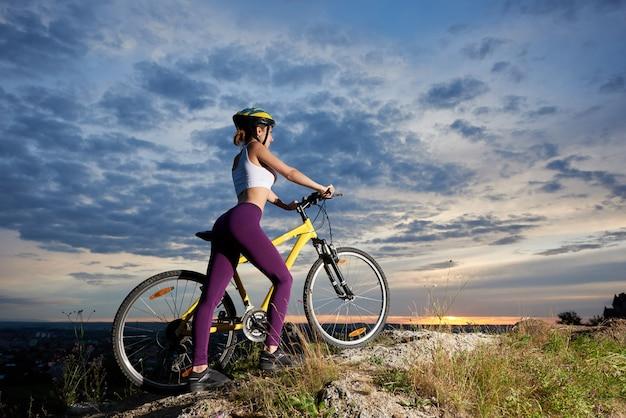 Спортивная девушка, стоя возле велосипеда и позирует на холме. стройная и красивая женщина. удивительный фон облачное небо. занятия спортом на свежем воздухе.