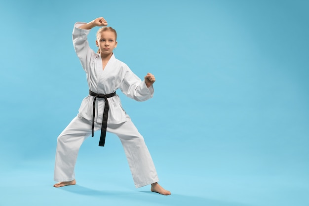 Sporty girl standing in stance and training karate in studio
