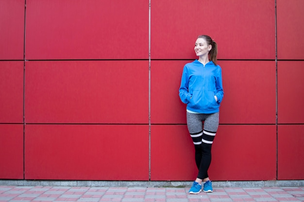 Sporty girl stands against a red wall in sportswear