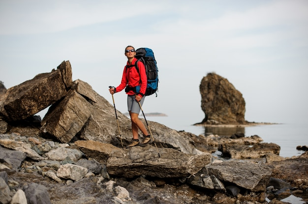 Sporty girl in sunglasses standing on the rock coastline on the sea with hiking backpack