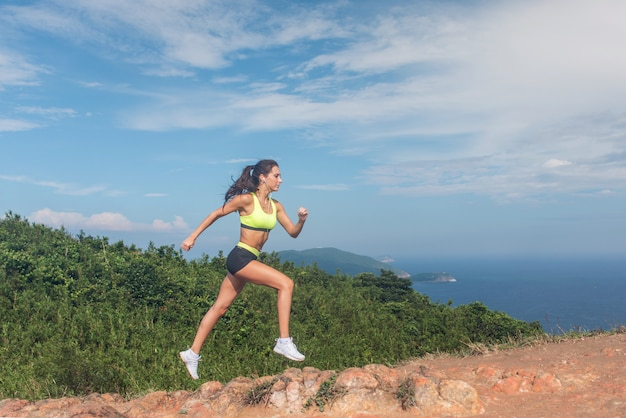 Sporty girl trail running on rocky path of the mountain sunny day.