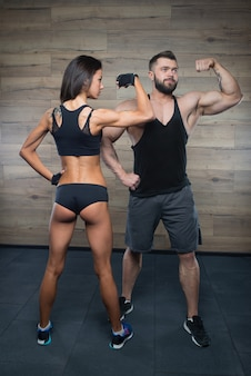 A sporty girl turned her back and a bodybuilder with a beard are demonstrating biceps in a gym