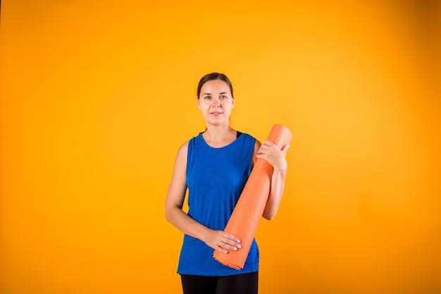 オレンジ色の壁にフィットネスマットでスポーティな女の子