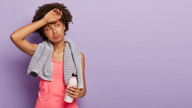 Sporty girl with afro hair wipes forehead, being sweaty, dressed in casual vest, holds bottle with fresh water, has regular training for keeping fit, wears towel on shoulders