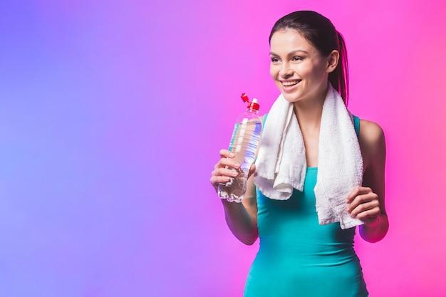 水のボトルと彼女の肩にタオルでスポーティな女の子。白い背景で隔離のフィットネスモデルの写真。