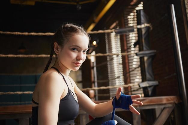 실내에 앉아 머리 띠, 그녀의 손에 붕대를 감싸고, 싸움을 준비하는 스포티 한 소녀. 블랙 탑에 아름 다운 젊은 sportswoman