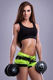 Sporty girl with dumbbells
