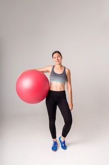 Sporty girl with a full-length fitness ball on a white