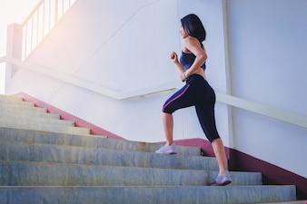 ジョギングすることによるスポーティな女の子の運動は階段を上げる。