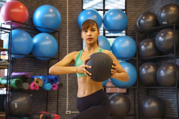 ジムでフィットネスボールで演習を行うスポーティな女の子。