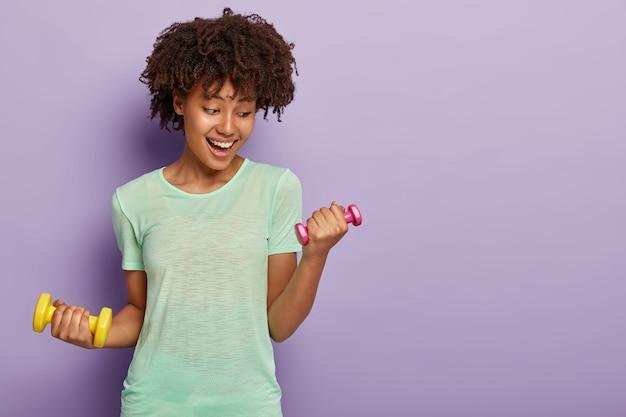 La ragazza sportiva e felice fa esercizi per i bicipiti con due piccoli manubri, vuole avere braccia muscolose