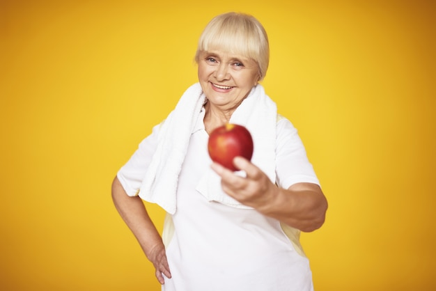 Sporty grandma offers apple exercises nutrition.