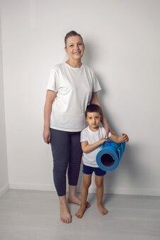 Спортивный внук и его бабушка стоят дома с ковриком для йоги Premium Фотографии