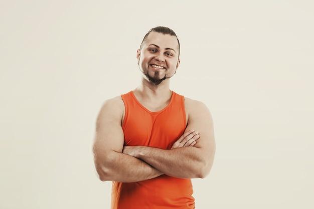 ジーンズとオレンジ色のtシャツのスポーティな男のボディービルダー