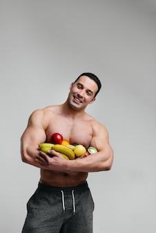 明るい果物と白でポーズスポーティな男。ダイエット。健康的なダイエット。