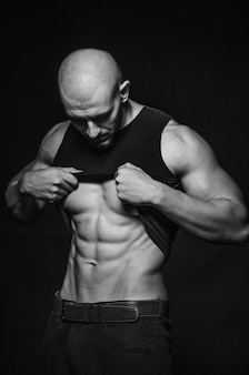 Sporty guy posing in the studio on the background. sports, beauty, black and white photography.