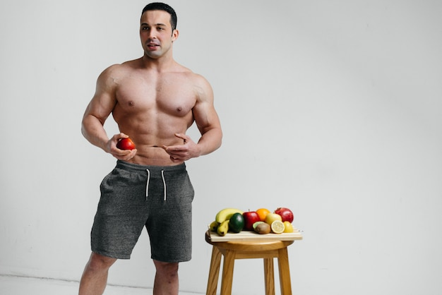 Sporty guy posing on white with bright fruits.