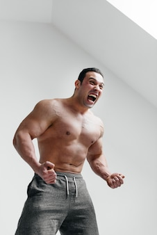 A sporty guy screams in rage against a white wall. anger. threat.