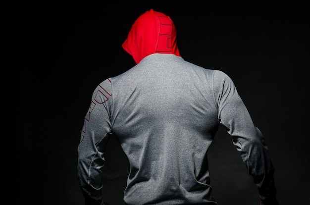 A sporty guy stands in the studio against a dark background in a hood. sports, beauty