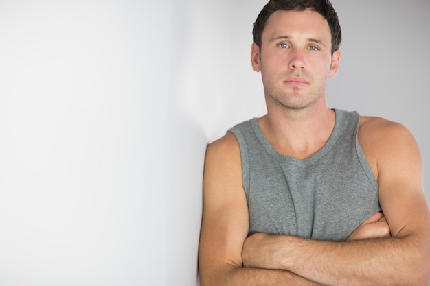 Sporty handsome man leaning against wall with arms crossed
