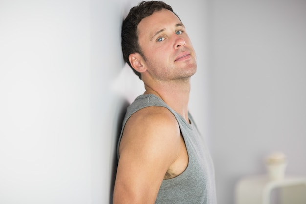 Sporty handsome man leaning against wall