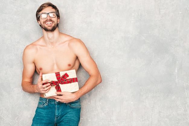 スポーティなハンサムな強い男。白い下着の灰色の壁の近くでポーズをとる健康的な運動フィットネスモデル。