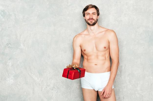 Спортивный красивый сильный мужчина. здоровая спортивная фитнес-модель позирует возле серой стены в белом нижнем белье.