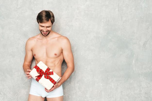 スポーティーなハンサムな強い男。白い下着の灰色の壁の近くでポーズをとる健康的な運動フィットネスモデル。