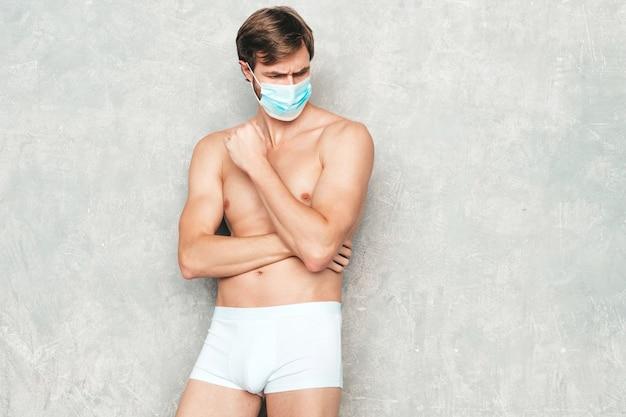 스포티 잘생긴 강한 남자. 흰색 속옷에 회색 벽 근처에서 포즈를 취하는 건강한 운동 피트니스 모델.