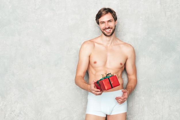 Sporty handsome strong man. healthy athletic fitness model posing near gray wall in white underwear.