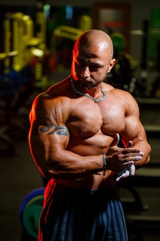 Спортивный красивый сильный мужчина позирует на фоне тренажерного зала. сильный бодибилдер с идеальным прессом, плечами, бицепсами, трицепсами и грудью.