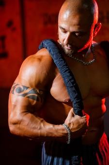 Спортивный красивый сильный мужчина позирует со спортивной веревкой на фоне тренажерного зала. сильный бодибилдер с идеальным прессом, плечами, бицепсами, трицепсами и грудью.