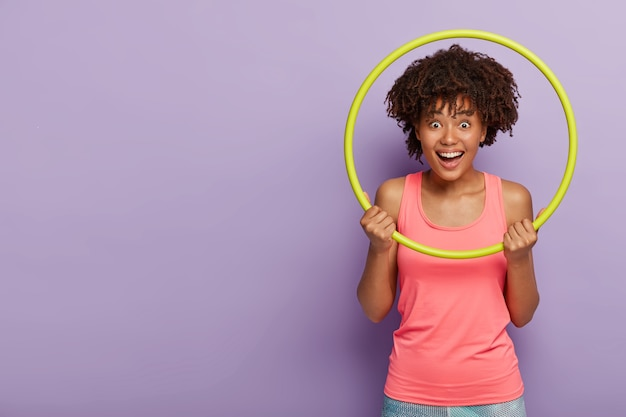 Sporty happy aro woman does exercises with hula hoop, laughs and enjoys rest