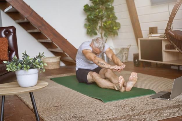 Спортивный здоровый мужчина средних лет делает упражнения на растяжку, сидя на коврике для йоги в гостиной