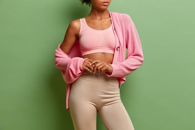 Sporty donna snella in buona salute indossa leggings superiori e maglione ha la pelle morbida essendo in buona forma corpo ben curato.
