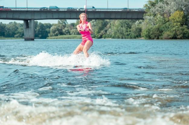 Спортивное хобби. молодая подтянутая женщина в розовом спасательном жилете занимается серфингом на вейкборде на реке, глядя перед собой