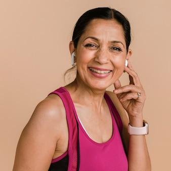 ワイヤレスイヤホンで音楽を聴くスポーティなインドの女性