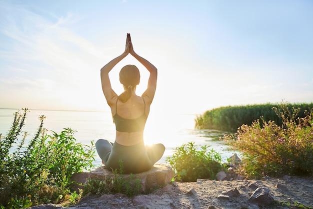 Спортивная дама сидит в позе лотоса и соединяет руки над головой, делая упражнения йоги в солнечный день на пляже