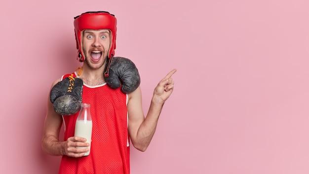 Stile di vita sportivo e concetto di scatola. il pugile maschio emotivo dimostra con un'espressione felice e meravigliata che apre la bocca ampiamente indica nell'angolo in alto a destra.