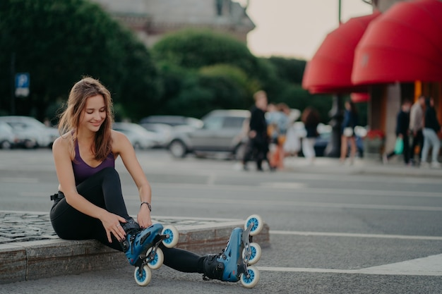 Sporty lifestyle and hobby. pleased dark haired european woman puts on inline skates going rollerblading